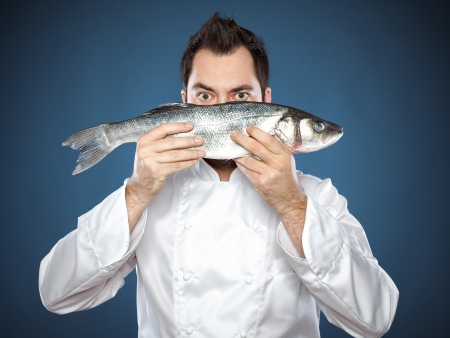 Young handsome chef with sea bass fish  photo