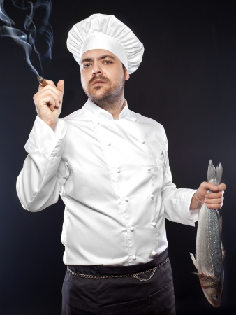 Young handsome chef with sea bass fish smoking cigar photo