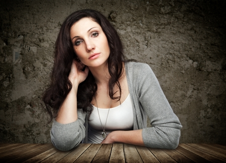 Beautiful young woman leaning on wooden table Stock Photo - 18359697