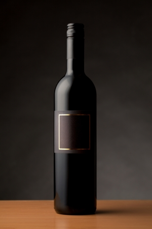 Black wine bottle with empty label isolated against dark background Stock Photo - 19843409