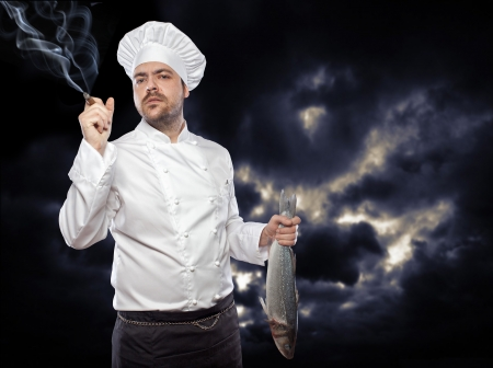 Young  chef with sea bass fish smoking cigar against dark sky photo