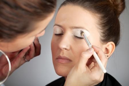 eye shade: Make-up artist applying white eye shade color with brush