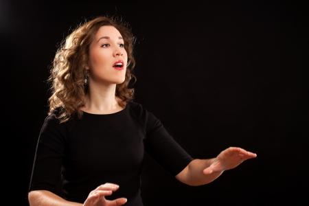 Vrouw koordirigent tijdens de uitvoering