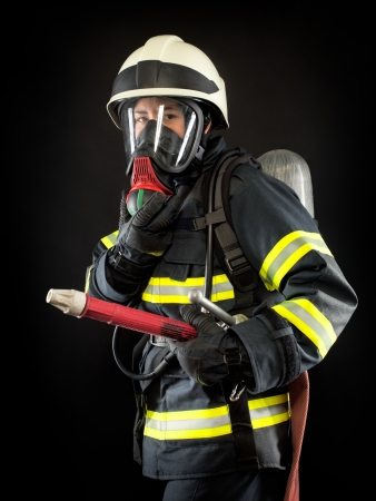 Firefighter wearing protective suit, helmet and mask photo