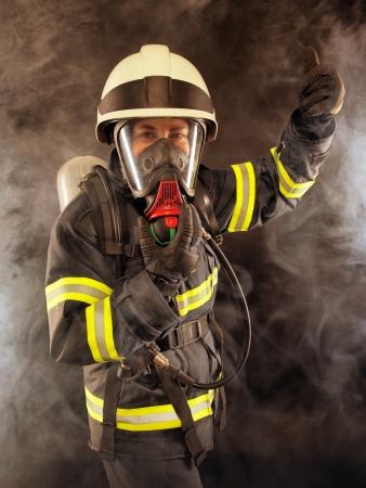 mascara de gas: Bombero con traje de protección, casco y máscara