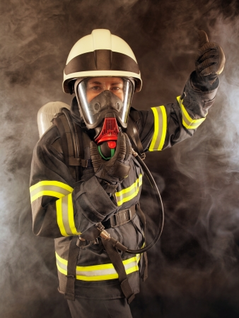 Firefighter wearing protective suit, helmet and mask