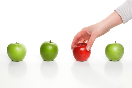 손 녹색 사과 사이 빨간 사과 따기