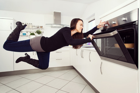 levitating: Young brunette woman in the kitchen levitating