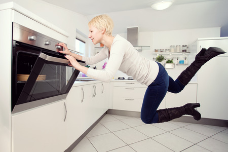 levitating: Young blond woman in the kitchen levitating Stock Photo