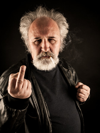 Grumpy man showing middle finger against black background photo