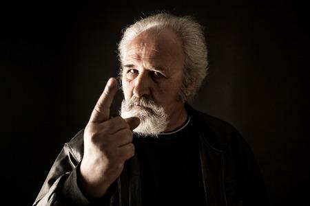 grumpy: Grumpy man against black background