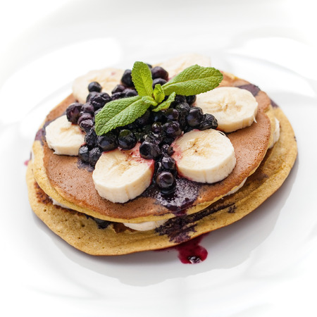 pancakes: Home made pancakes with banana and frozen blueberries Stock Photo