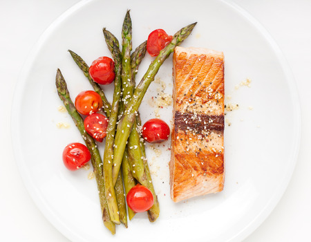 white sesame seeds: Salmon fillet with asparagus and cherry tomatoes on white plate