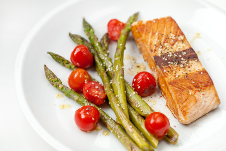 pink salmon: Salmon fillet with asparagus and cherry tomatoes on white plate