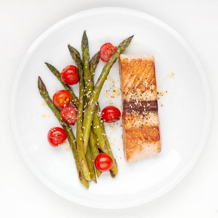 plate of food: Filetto di salmone con asparagi e pomodorini sul piatto bianco