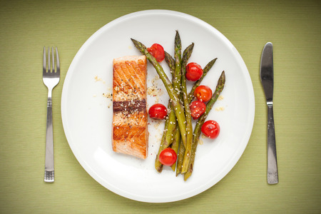 Salmon fillet with asparagus and cherry tomatoes on white plate photo