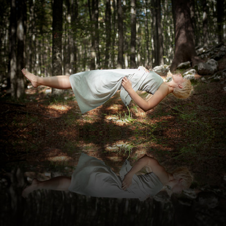 Levitating woman in the forest above water
