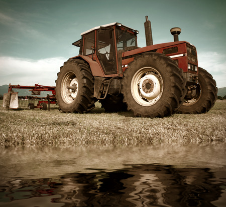 old tractors: Tractor on field near water pond