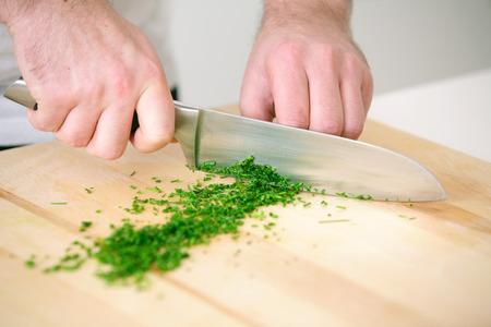 bulb and stem vegetables: Chef chopping parsley on wodden board  Stock Photo