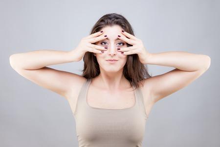 Beautiful young caucasian woman doing face yoga pose Standard-Bild