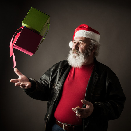 big ass: Grumpy Santa Claus with gift boxes and cigarette Stock Photo