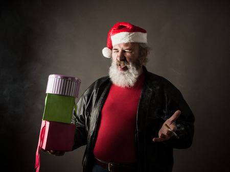 ass christmas: Grumpy Santa Claus with gift boxes and cigarette Stock Photo