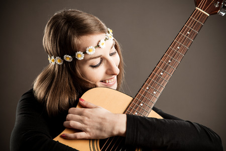 Young woman with acoustic guitar and flower hairband photo