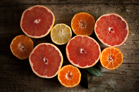 Different kind of citrus fruits on wooden board