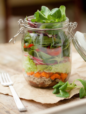 Lettuce, tomato and other vegetables in glass jar 免版税图像