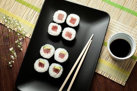 sushi plate: maki sushi on black plate with chopsticks