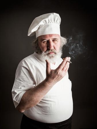 grumpy old man: Grumpy old chef smoking against dark background