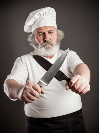 grouchy: Grumpy old chef with two knives against dark background