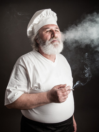grouchy: Grumpy old chef smoking against dark background