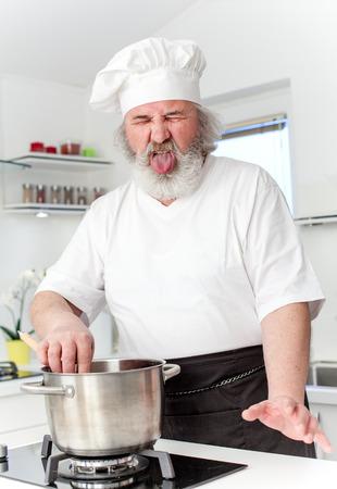 grumpy old man: Elderly chef in kithen preparing food Stock Photo