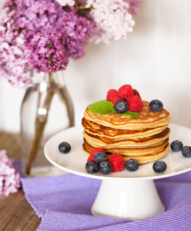 pancakes: Pile of pancakes with fresh berries on white plate