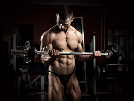 muscle guy: Strong bodybuilder with barbell in the gym Stock Photo