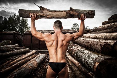 hombre fuerte: Hombre musculoso fuerte sosteniendo troncos de madera pesada