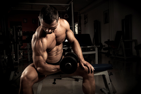 lifter: Strong bodybuilder with dumbbell in the gym