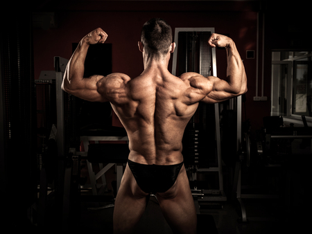 Strong bodybuilder flexing his back in the gym Stock Photo