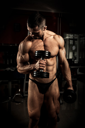dumb: Strong bodybuilder with dumbbells in the gym Stock Photo