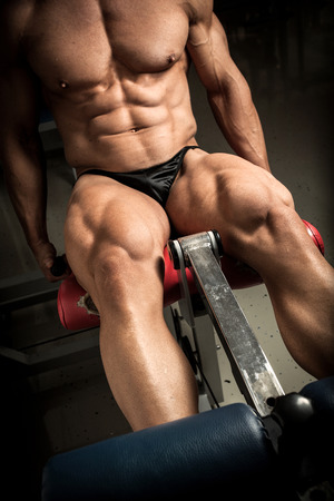 quadriceps: Strong bodybuilder training quads in the gym