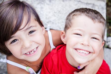Little siblings with big smiles and missing milk teeth