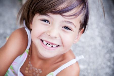 큰 미소와 누락 우유 이빨을 가진 어린 소녀