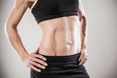 body torso: Torso of strong female body against gray background