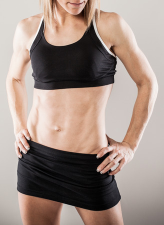 Torso of strong female body against gray background