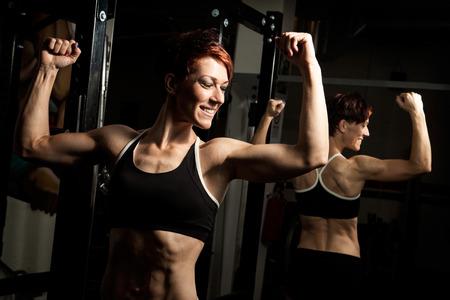 school gym: Young fit caucasian female bodybuilder in old school gym