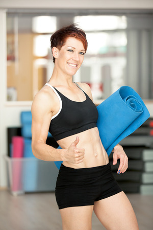 fit muscular woman posing at the gym photo