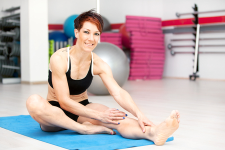 Fit woman stretching after workout at the gym photo
