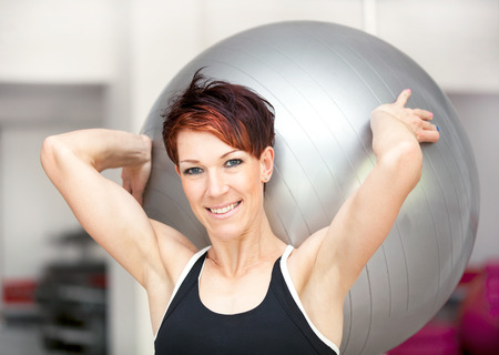 weight lifter: Fit woman with ball at the gym Stock Photo