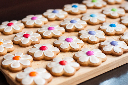 biscuit biscuits: Gingerbread cookie flowers with candy on wooden board